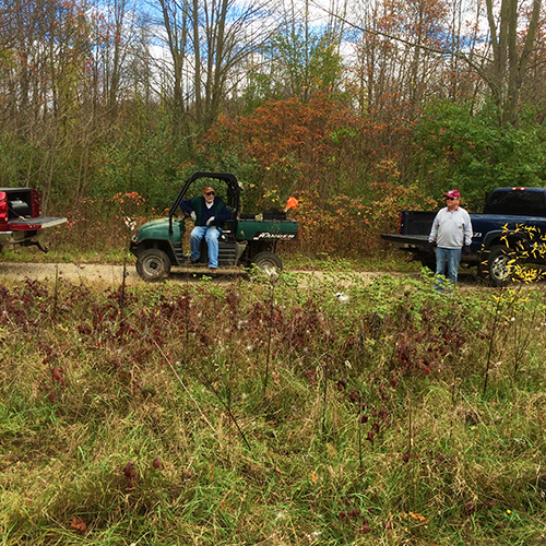 Volunteers carry tools, caging material, and trees on ATV's as they stop at each fitness station to do the plantings.